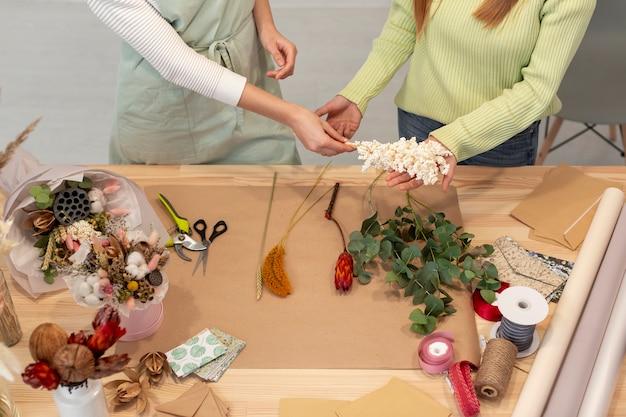 Высокий вид деловых женщин, управляющих цветочным магазином