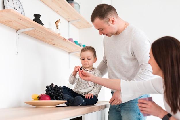 両親とキッチンで果物を食べる赤ちゃん