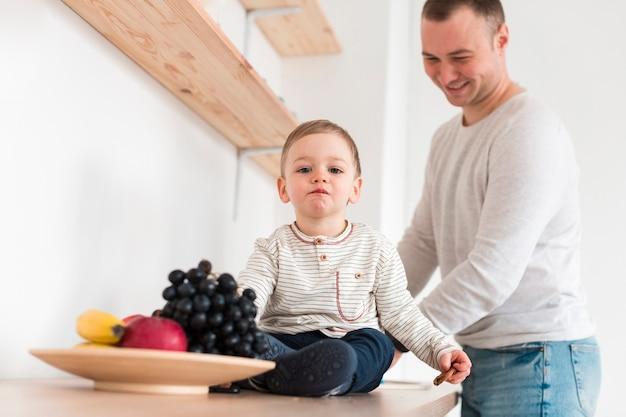 父と赤ちゃんの果物とキッチンで
