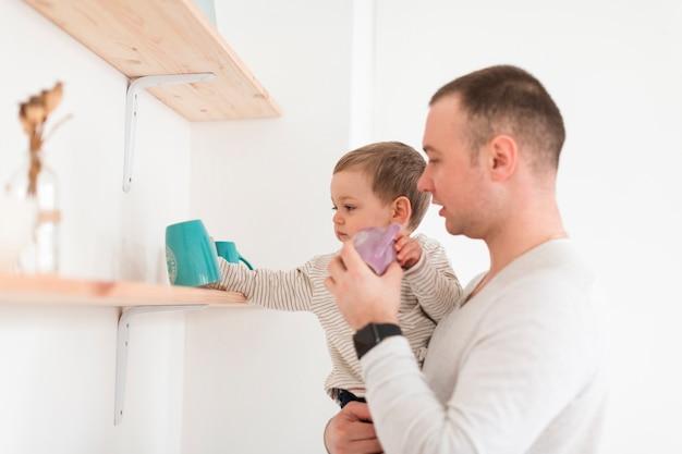 子供とマグカップを保持している父の側面図