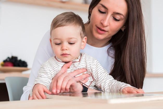 Вид спереди матери с ребенком на кухне