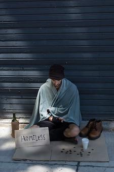 Бездомный мужчина с бутылкой алкоголя и монетами