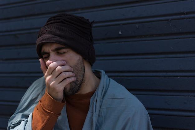 Бездомный мужчина зевает и прикрывает рот