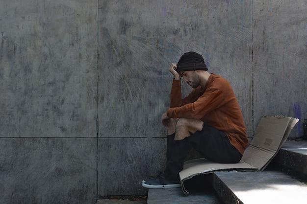 Бездомный мужчина сидит боком на картоне