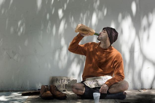 Бездомный мужчина пьет алкогольный напиток