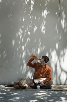 Бездомный мужчина пьет алкоголь из бутылки