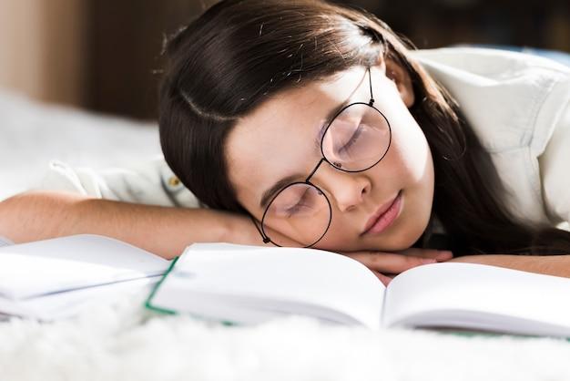 眠っている眼鏡を持つ若い女の子をクローズアップ