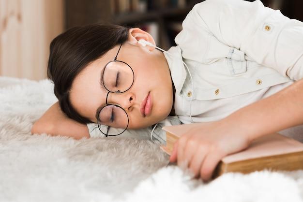 眠っているクローズアップの疲れている若い女の子
