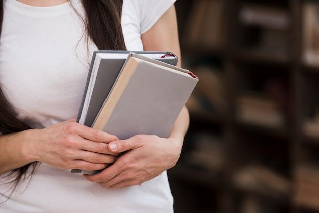 彼女の手で本を保持しているクローズアップの女性