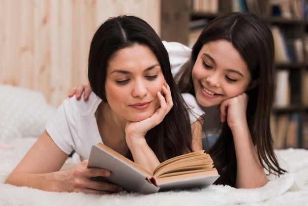 正面の大人の女性と本を読んでいる女の子