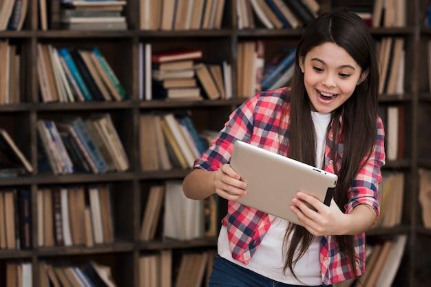Молодая девушка играет на планшете в библиотеке