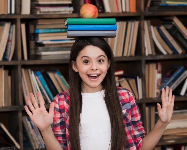 Симпатичная молодая девушка держит книги на голове