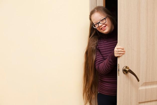 Улыбающаяся девушка с синдромом дауна позирует во время открытия двери