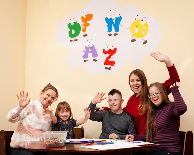 Счастливые дети с синдромом дауна машут руками и позируют