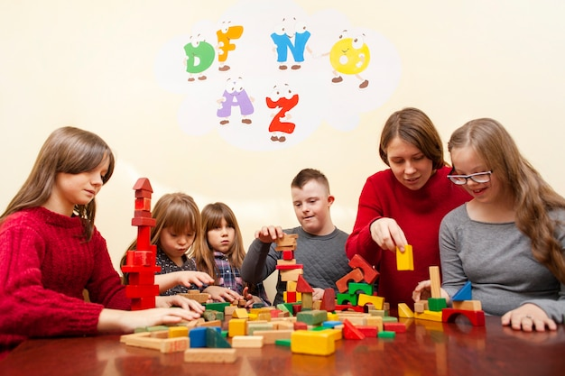 Дети с синдромом дауна играют с разноцветными кубиками