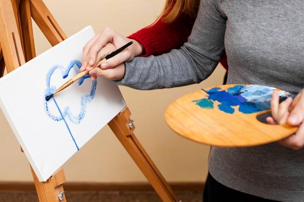 Девушка помогает девушке с краской синдрома дауна