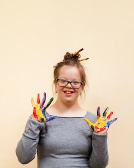 カラフルな手のひらを見せながらポーズをとってダウン症候群を持つ少女