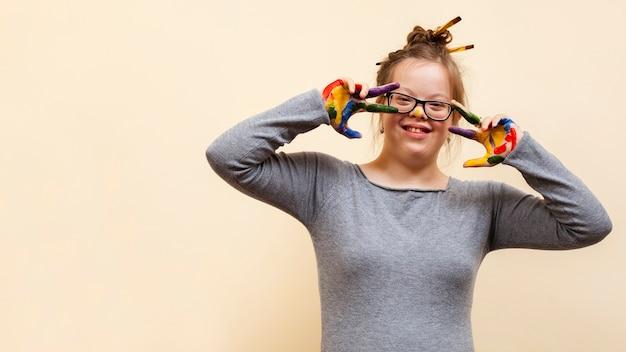 Счастливая девушка с синдромом дауна позирует с разноцветными ладонями