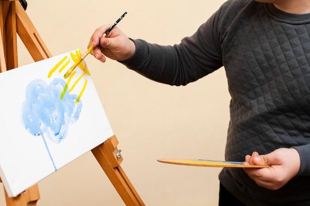 パレットと絵画を保持しているダウン症候群を持つ少年の側面図