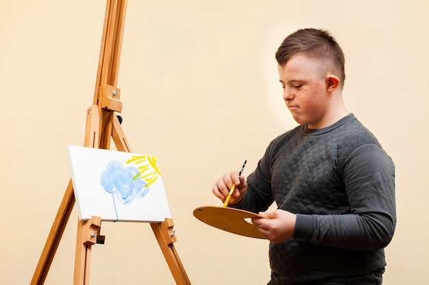 ダウン症の絵を持つ少年の側面図