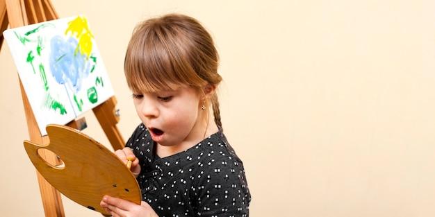Девушка с синдромом дауна держит палитру и живопись