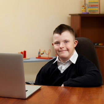 Мальчик с синдромом дауна позирует с ноутбуком