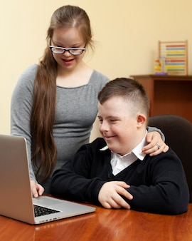 Мальчик и девочка с синдромом дауна, глядя на ноутбук