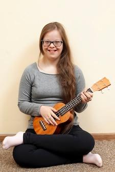Девушка с синдромом дауна держит гитару и улыбается