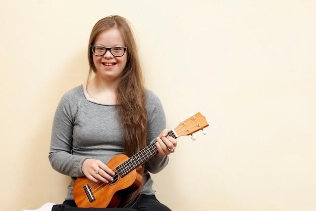 Улыбающаяся девушка с синдромом дауна держит гитару