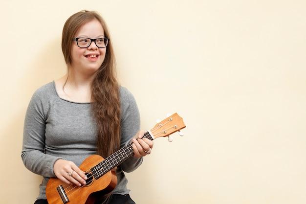 Счастливая девушка с синдромом дауна держит гитару