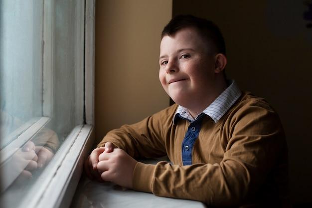 ウィンドウでポーズをとってダウン症候群の少年