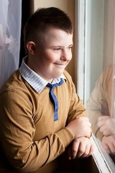 ウィンドウでポーズをとってダウン症候群の幸せな少年の側面図