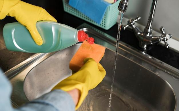 Женщина в резиновых перчатках чистит раковину