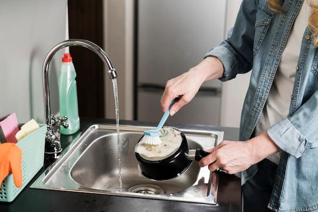 Женщина чистит горшок в раковине с помощью кисти