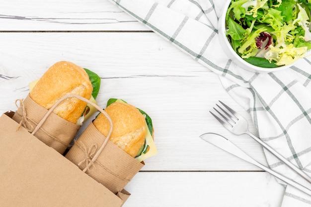 Вид сверху бумажный пакет с двумя бутербродами внутри и салат