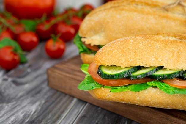 Два бутерброда с ломтиками огурца и расфокусированные помидоры