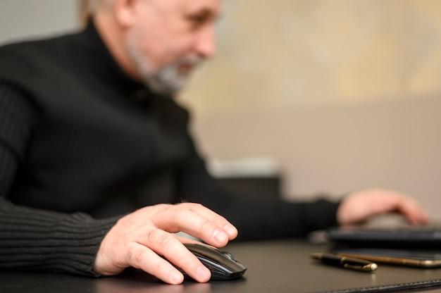 Зрелый человек работает на ноутбуке с помощью мыши
