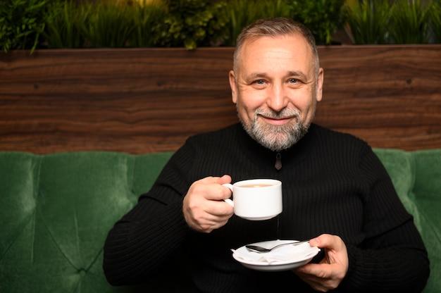 Мужчина держит чашку кофе в ресторане