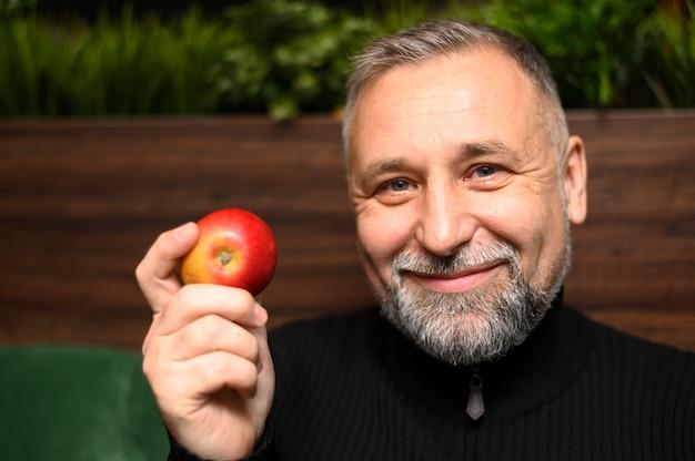 Зрелый мужчина держит яблоко
