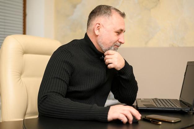 Боком зрелый человек, работающий на своем столе