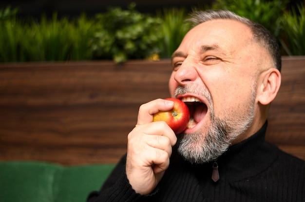 Зрелый человек ест яблоко