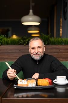 Зрелый человек ест в суши-ресторане