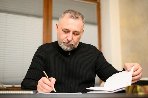 Зрелый человек пишет на ноутбуке