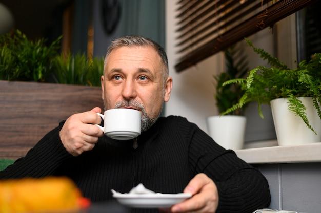 Зрелый человек пьет кофе