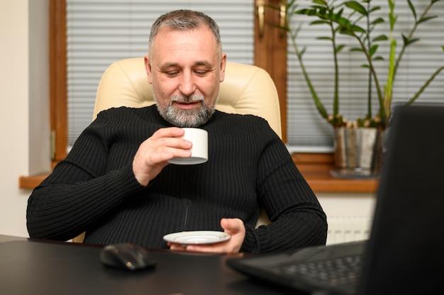 Зрелый человек, держа чашку кофе у себя дома