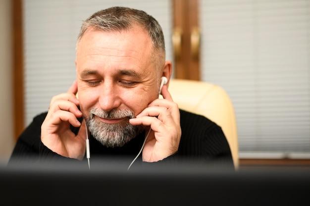 Смайлик зрелый человек слушает музыку