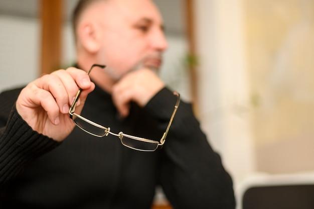Зрелый человек держит очки