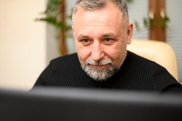 Зрелый человек, глядя через свой компьютер