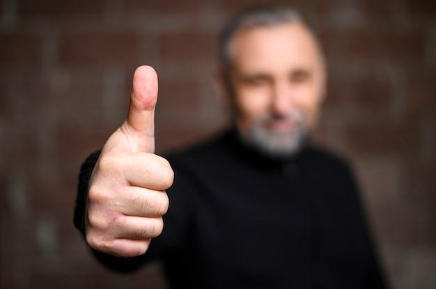 Зрелый человек, делая пальцы вверх знак