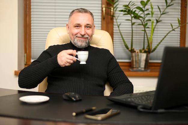 Человек сидит за столом с чашкой кофе